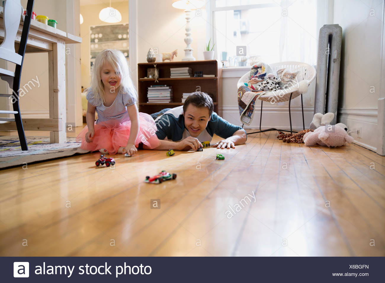 Father and daughter racing toy cars on floor - Stock Image