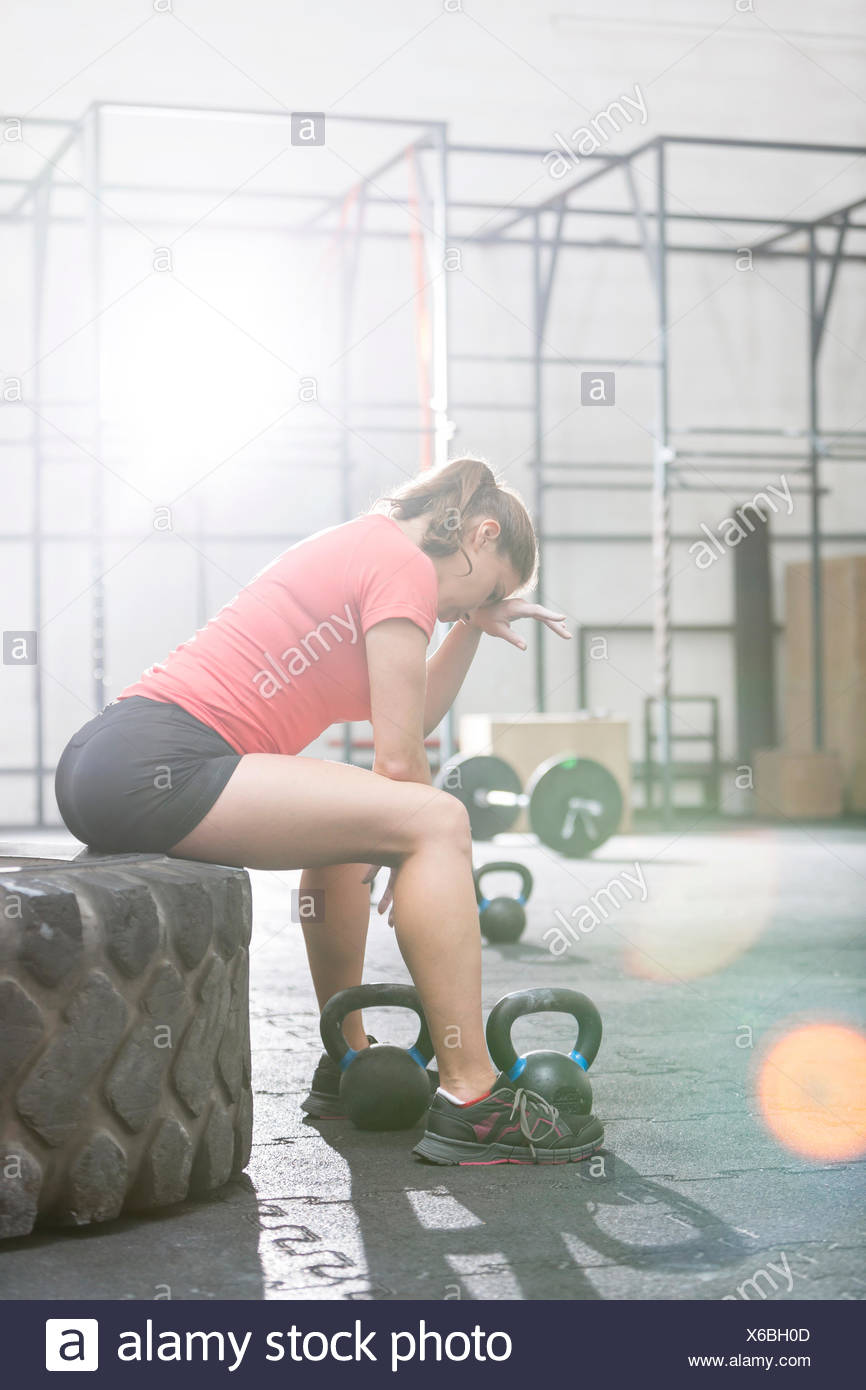 Tired woman sitting on tire in crossfit gym - Stock Image