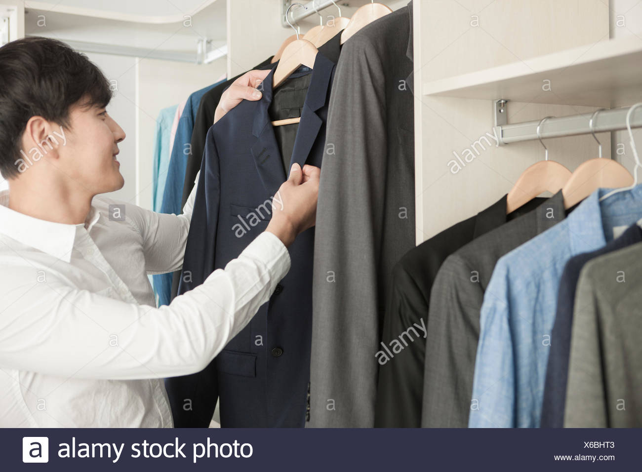 Man Holding A Jacket From The Closet And Looking At The Jacket   Stock Image