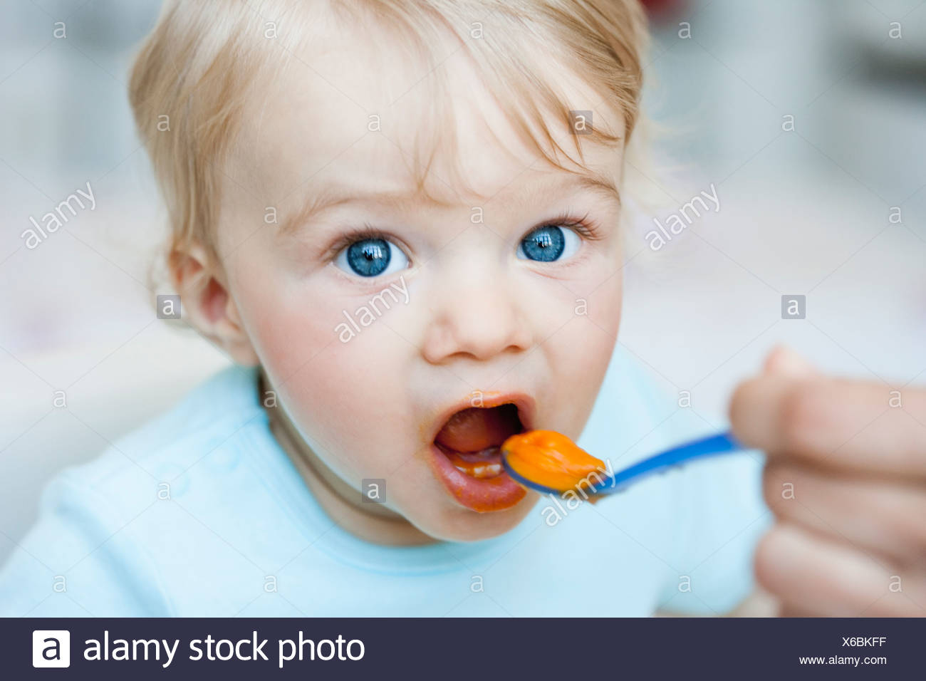 baby being fed looking at viewer - Stock Image