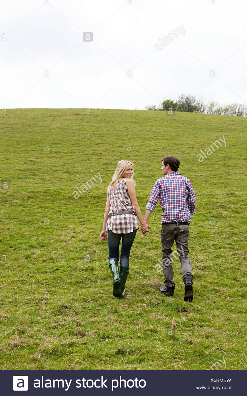 Young couple walking up hill - Stock Image