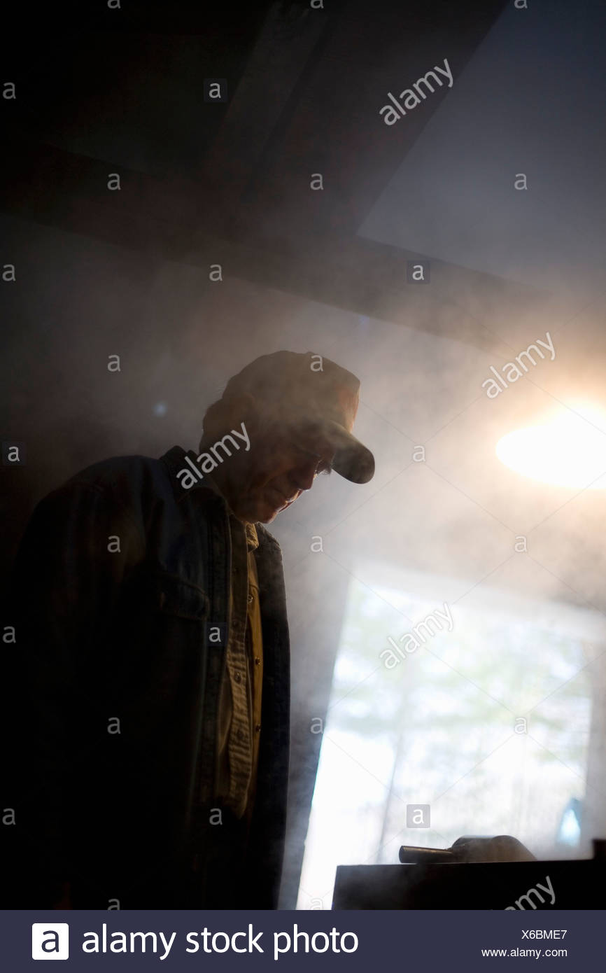 Senior man standing in front of a furnace - Stock Image