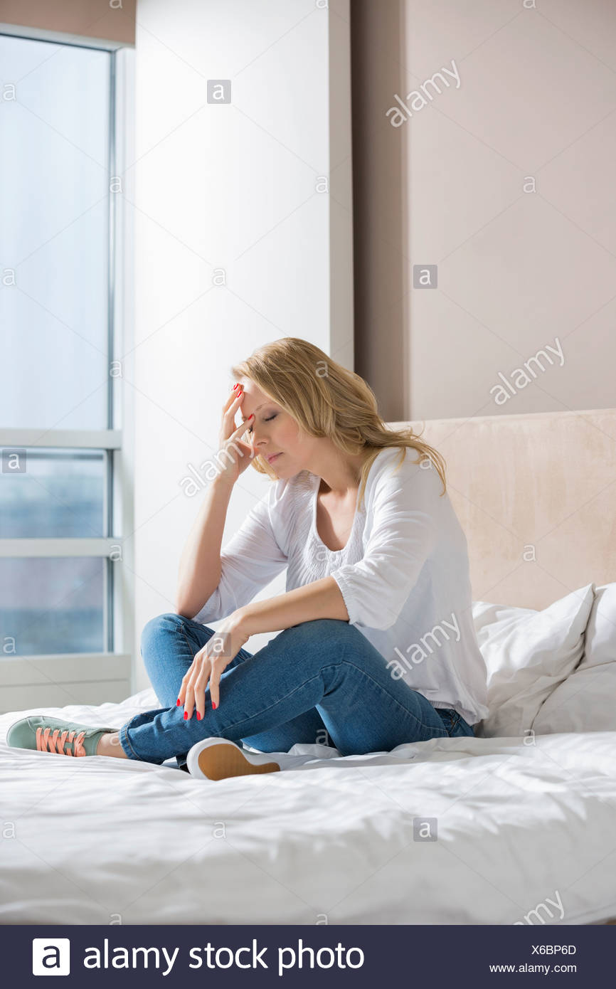 Full length of stressed woman with hand on face sitting on bed - Stock Image