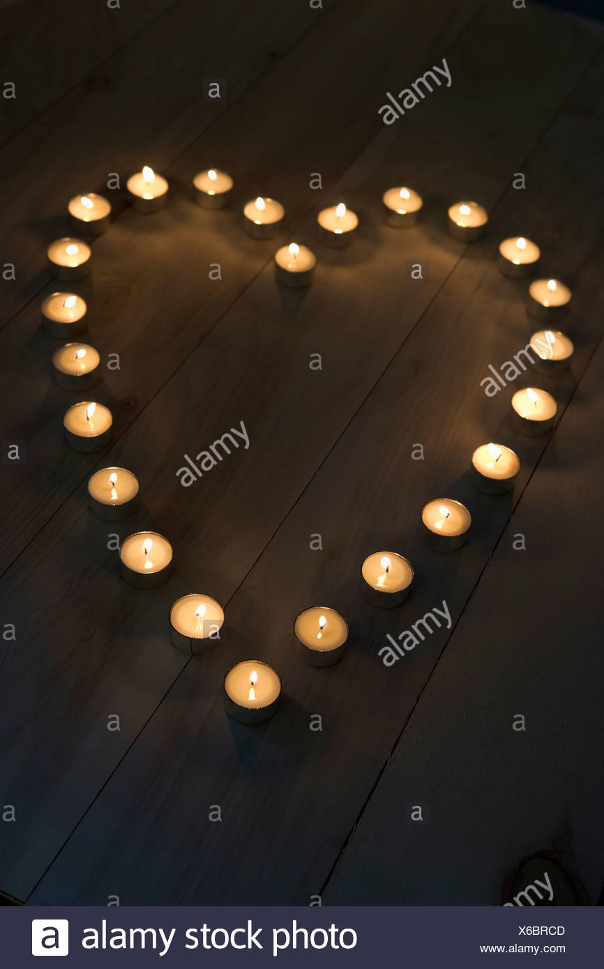 Illuminated Candles Placed In A Heart Shape - Stock Image
