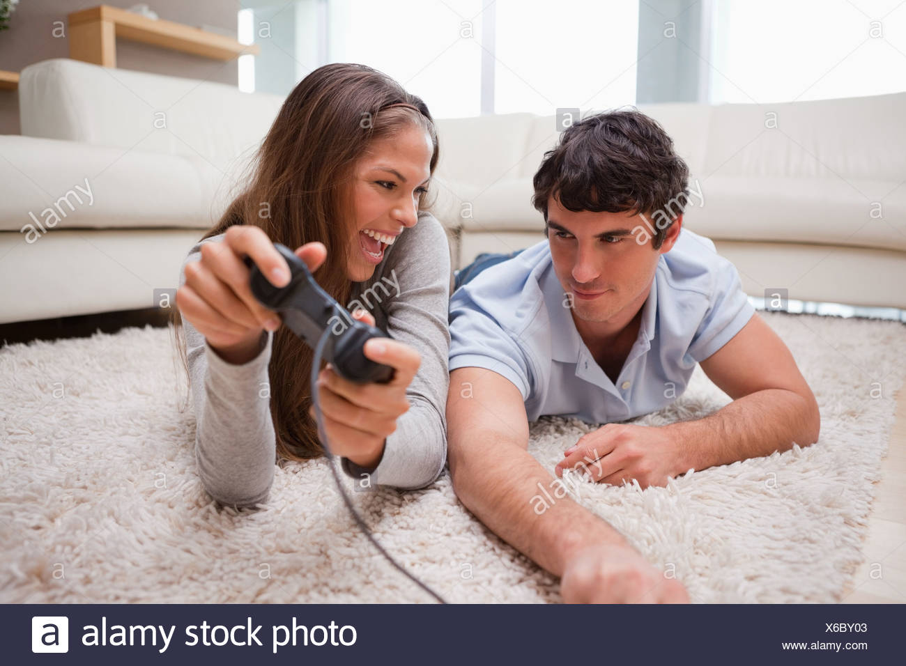 Woman just defeated her boyfriend at a video game - Stock Image