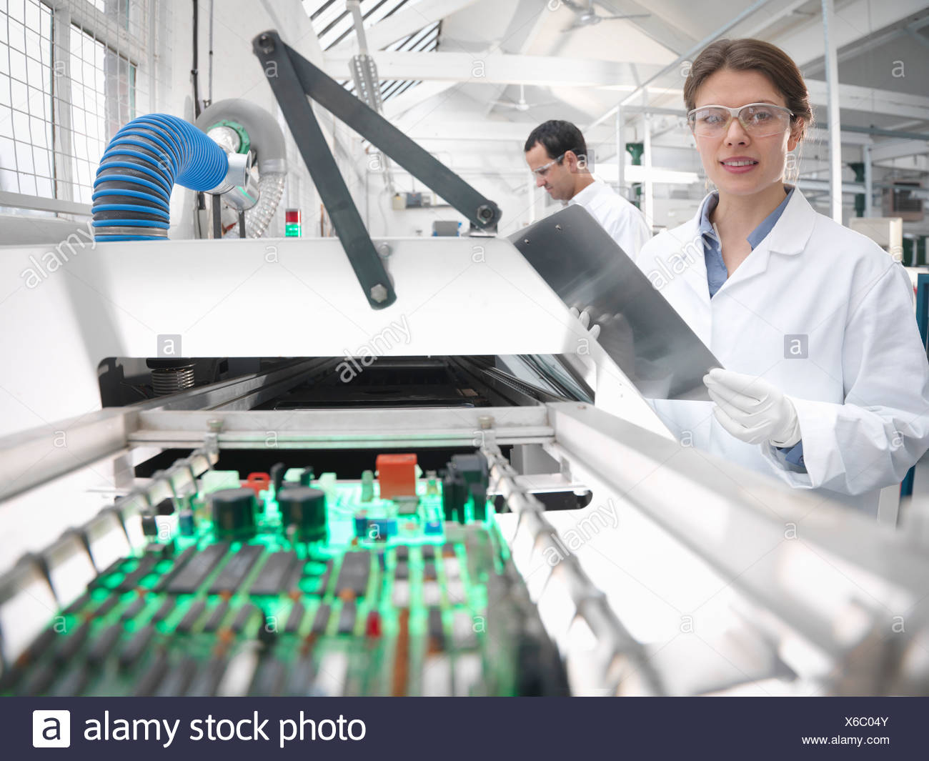 Workers with automated soldering machine - Stock Image