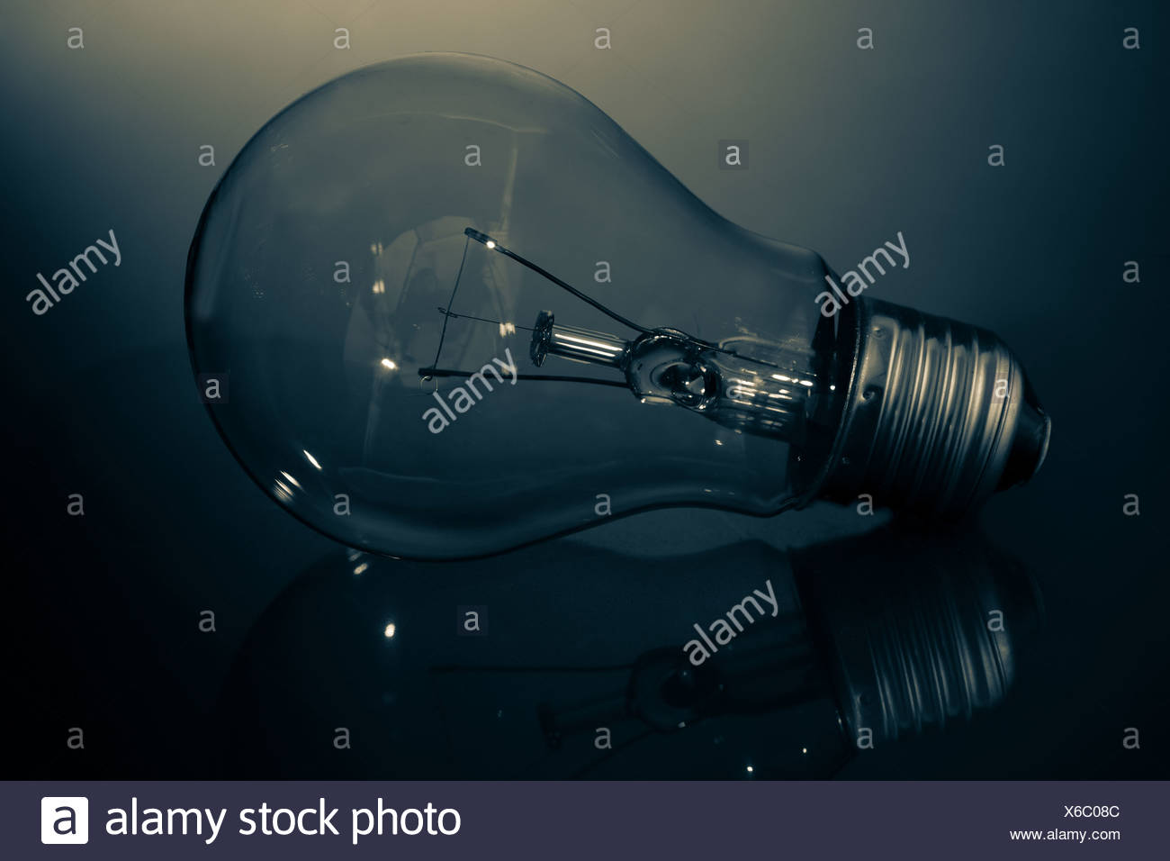 Clear light bulb lay on its side in darkness - Stock Image