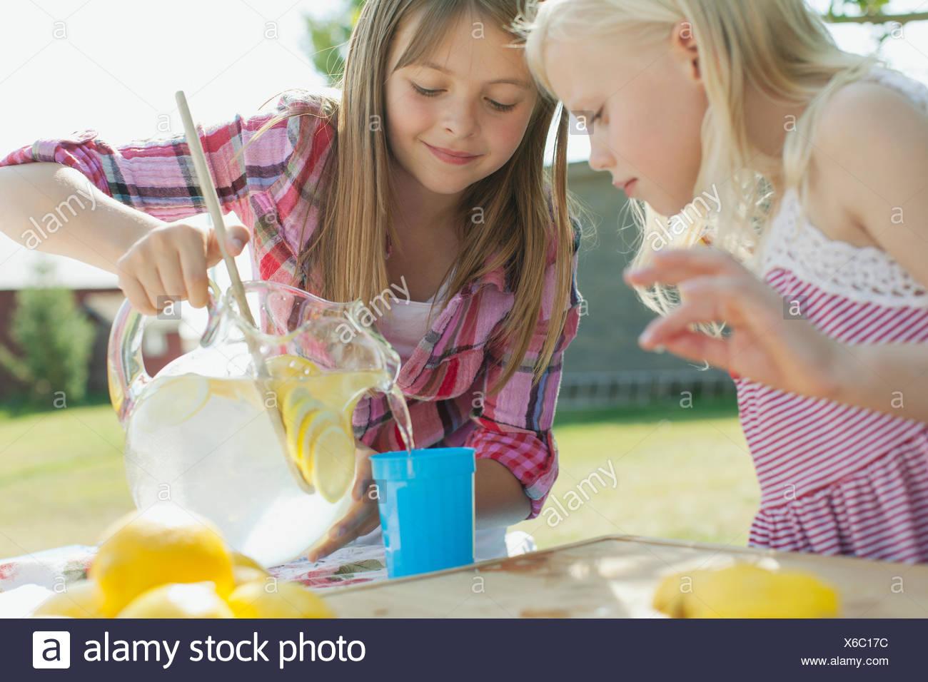 Sisters making lemonade together. - Stock Image