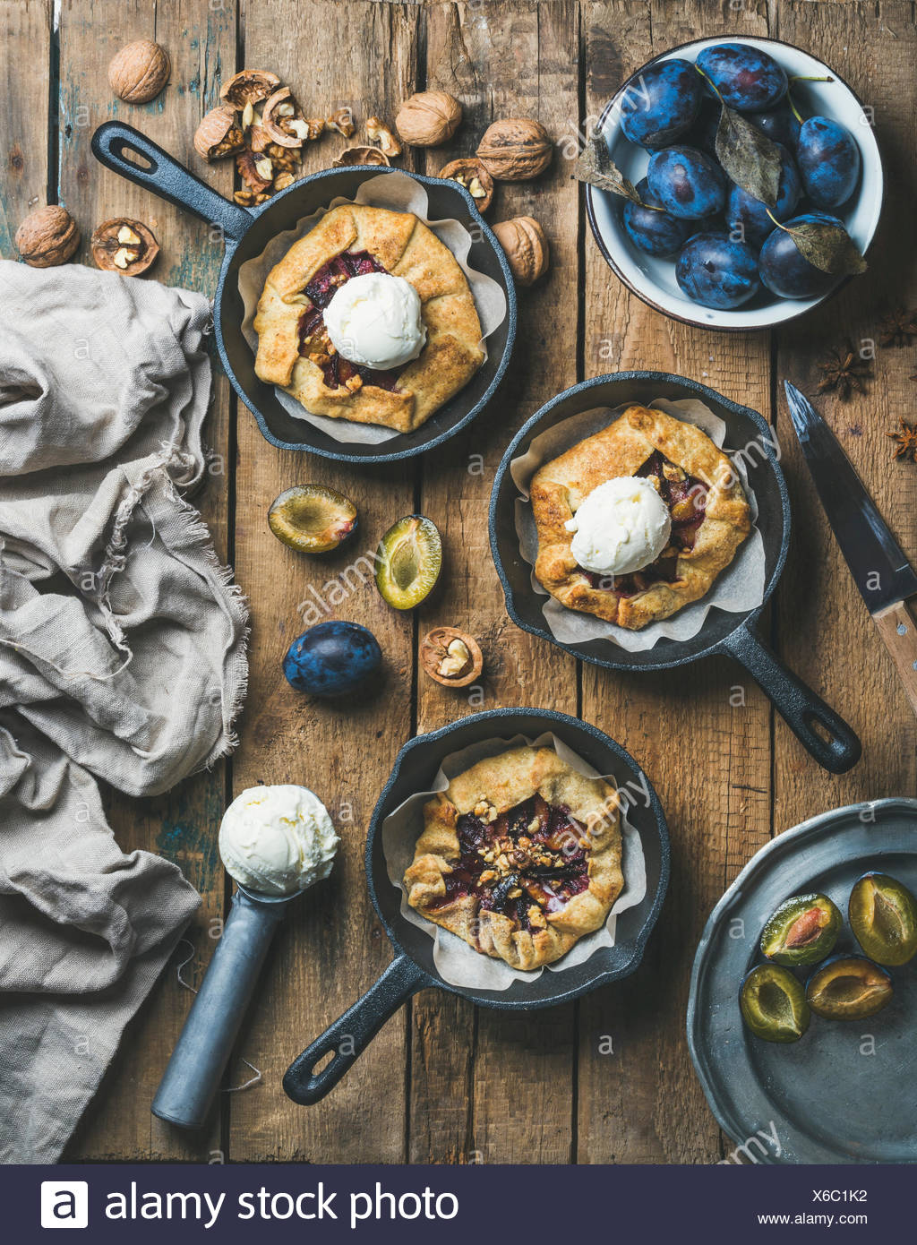 Plum and walnut crostata pie with ice-cream scoops in individual cast iron pans over rustic wooden table, top view. Slow food concept - Stock Image
