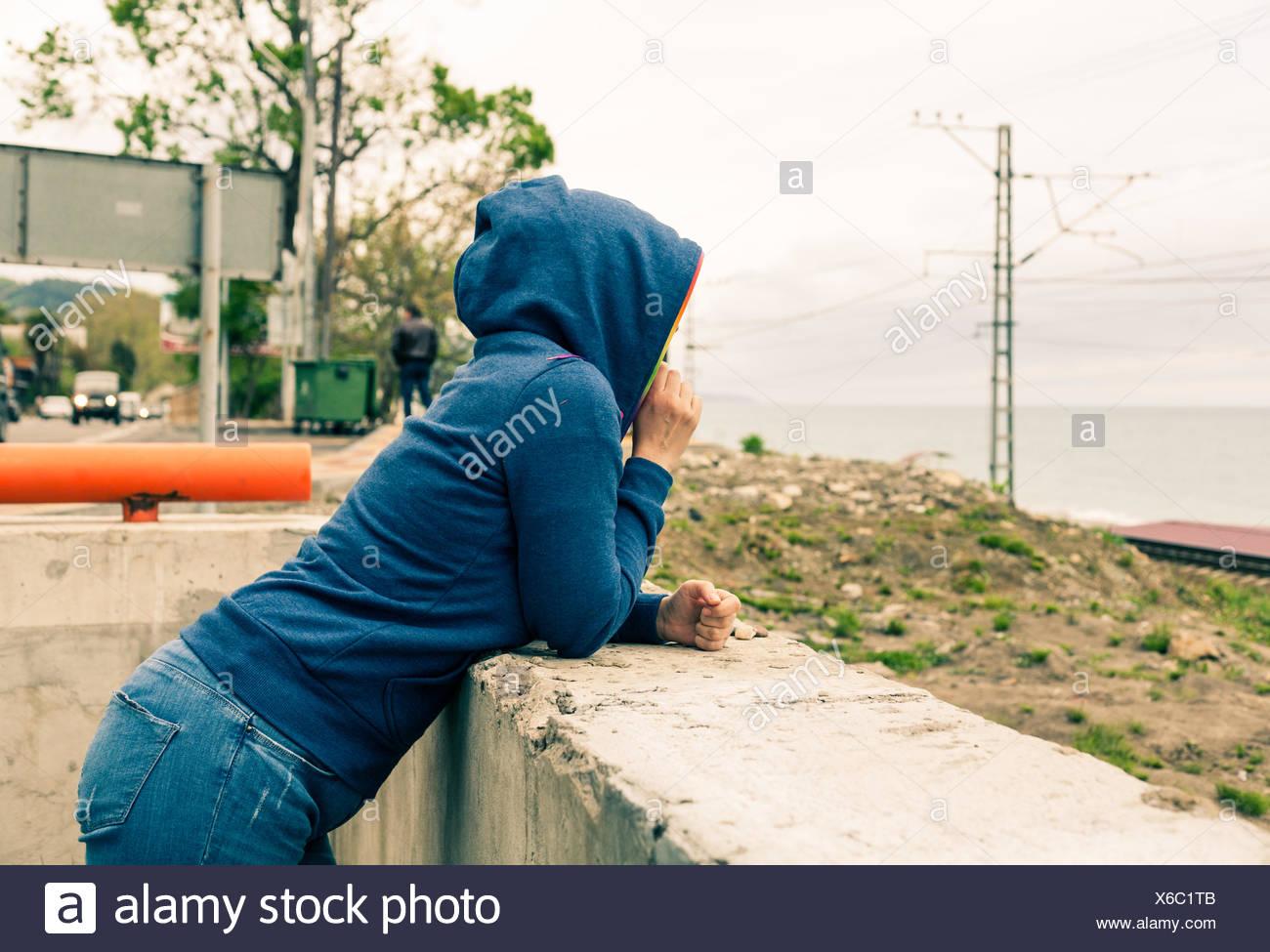 Women in hoody looking at horizon - Stock Image