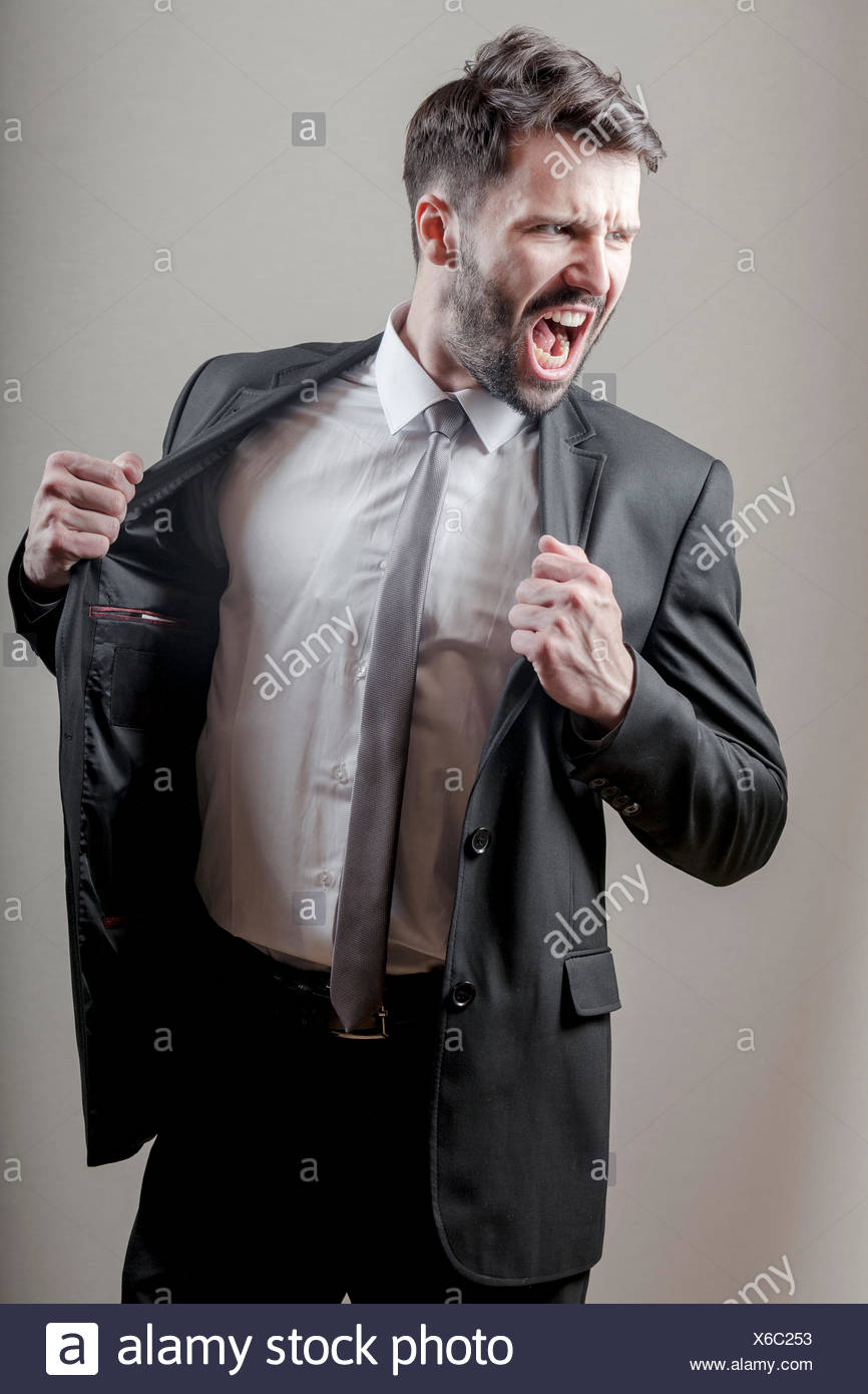 Businessman screaming while clenching fists - Stock Image
