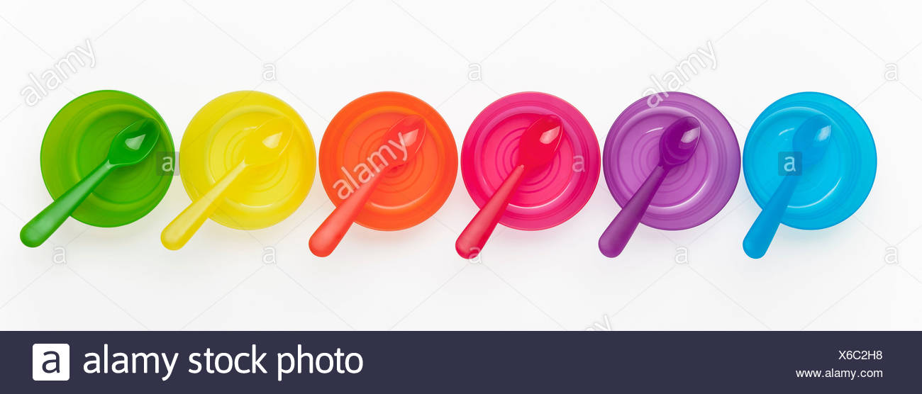 Colourful plastic spoons and bowls in a row - Stock Image