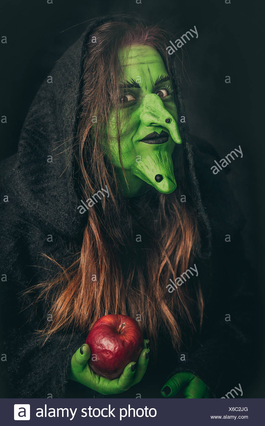 Evil witch holding a rotten apple - Stock Image