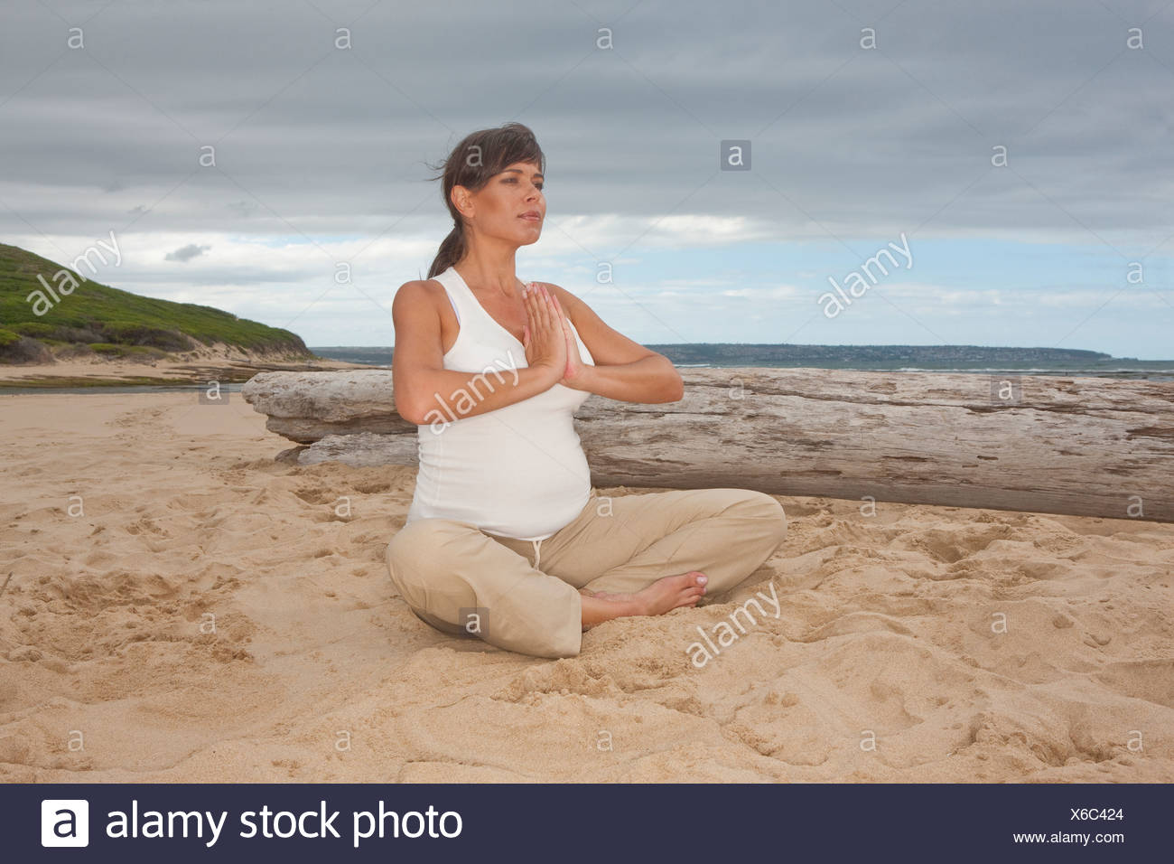 Pregnant mid adult woman practicing yoga on beach Stock Photo