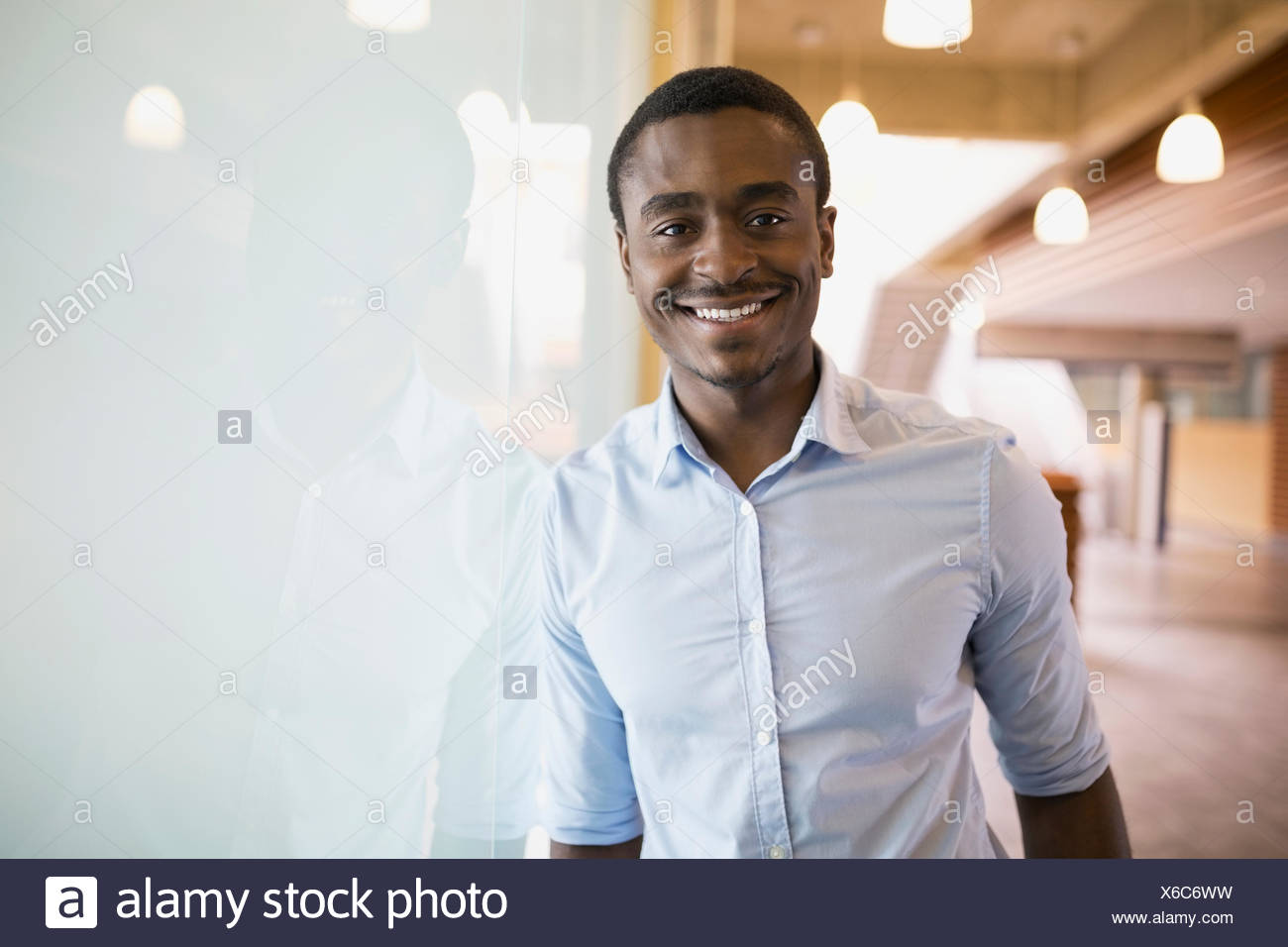 Portrait smiling businessman leaning on frosted glass - Stock Image