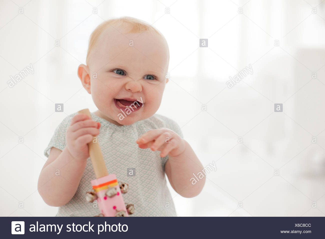 Smiling baby sitting on floor Stock Photo