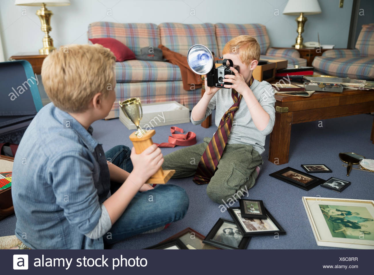 Brothers playing with old camera and trophy memorabilia - Stock Image