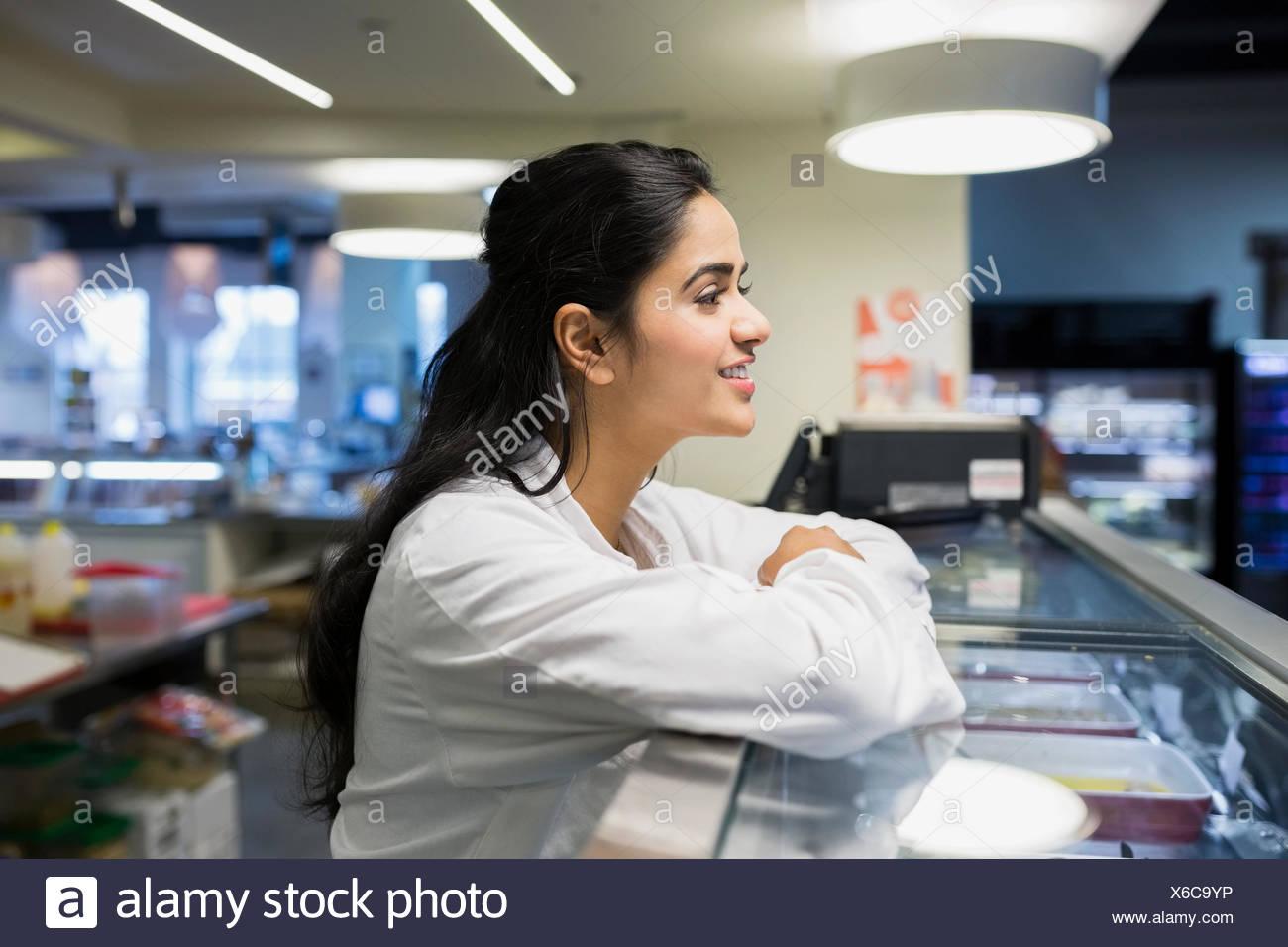 Smiling worker behind deli case - Stock Image