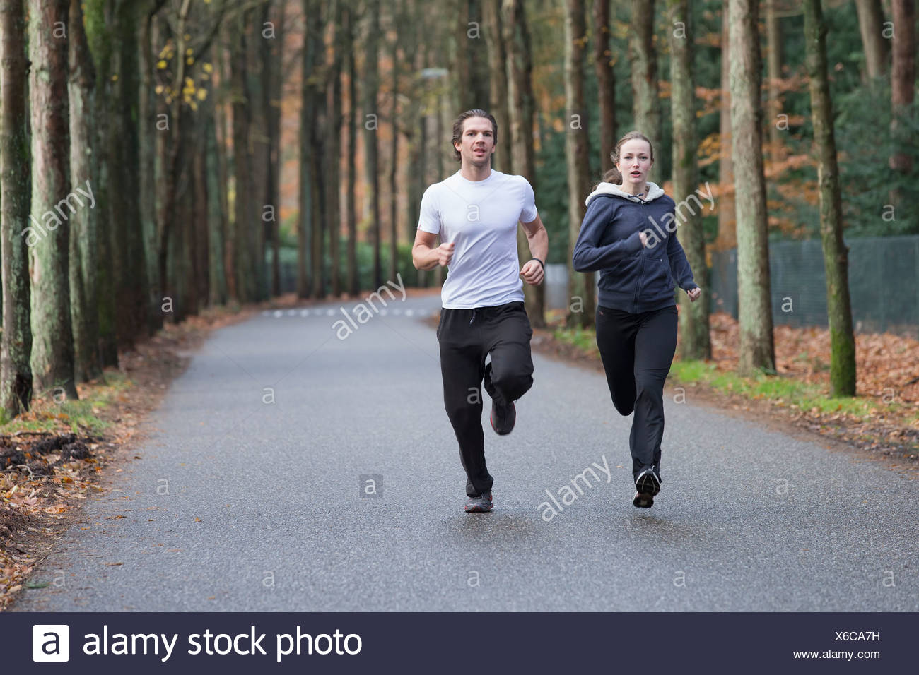 Couple running through forest - Stock Image