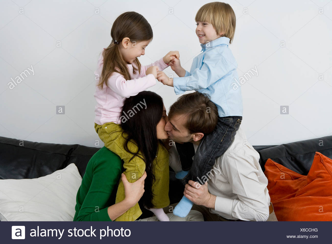 Two parents carrying children on their shoulders and kissing - Stock Image
