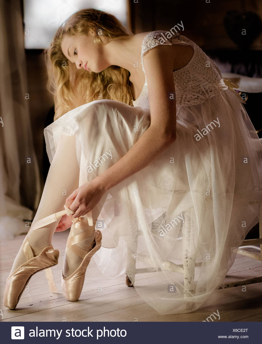 Young ballet dancer in white dress preparing ribbons on ballet shoes - Stock Image