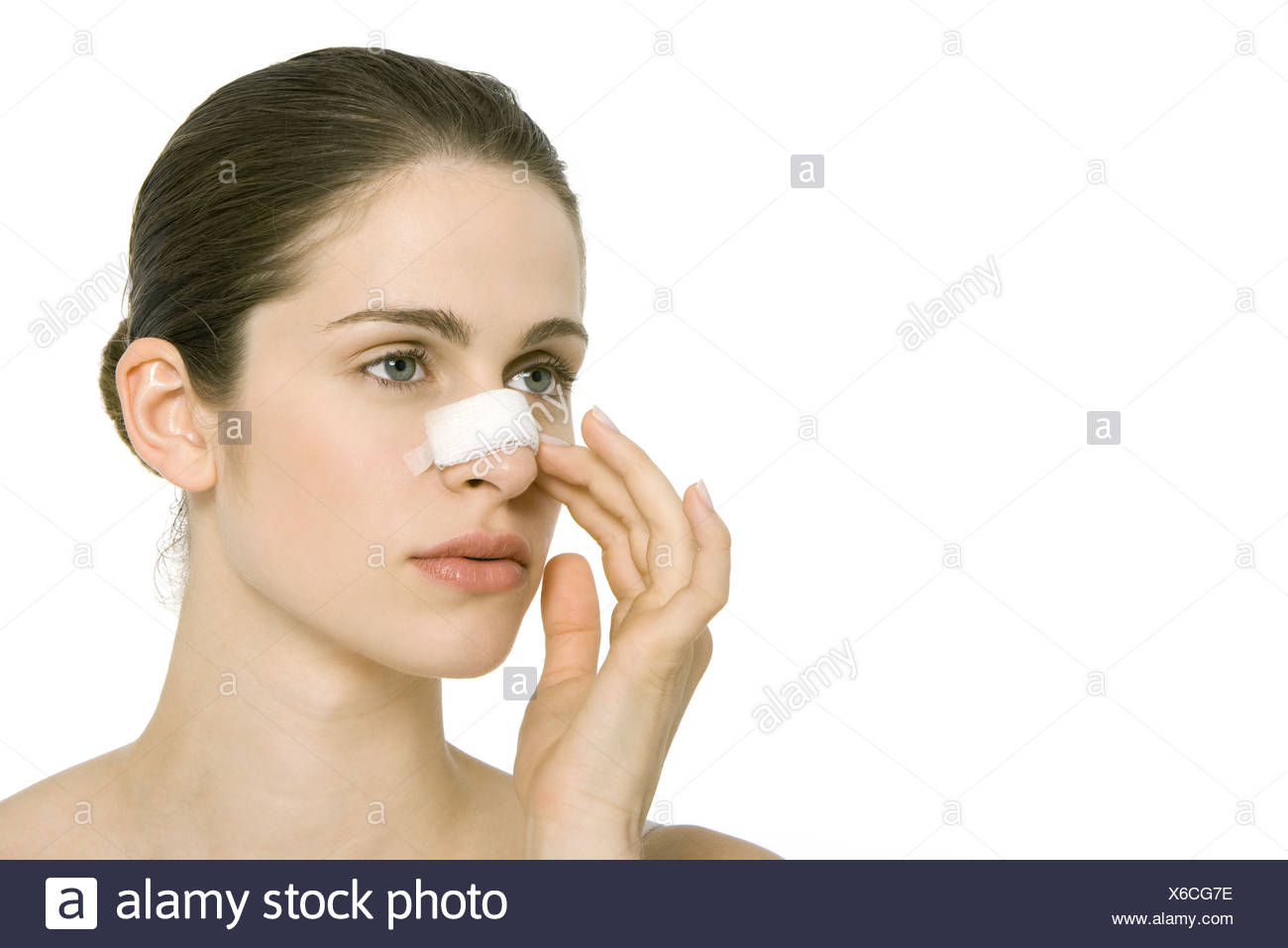 Young woman with bandage on nose, looking away - Stock Image