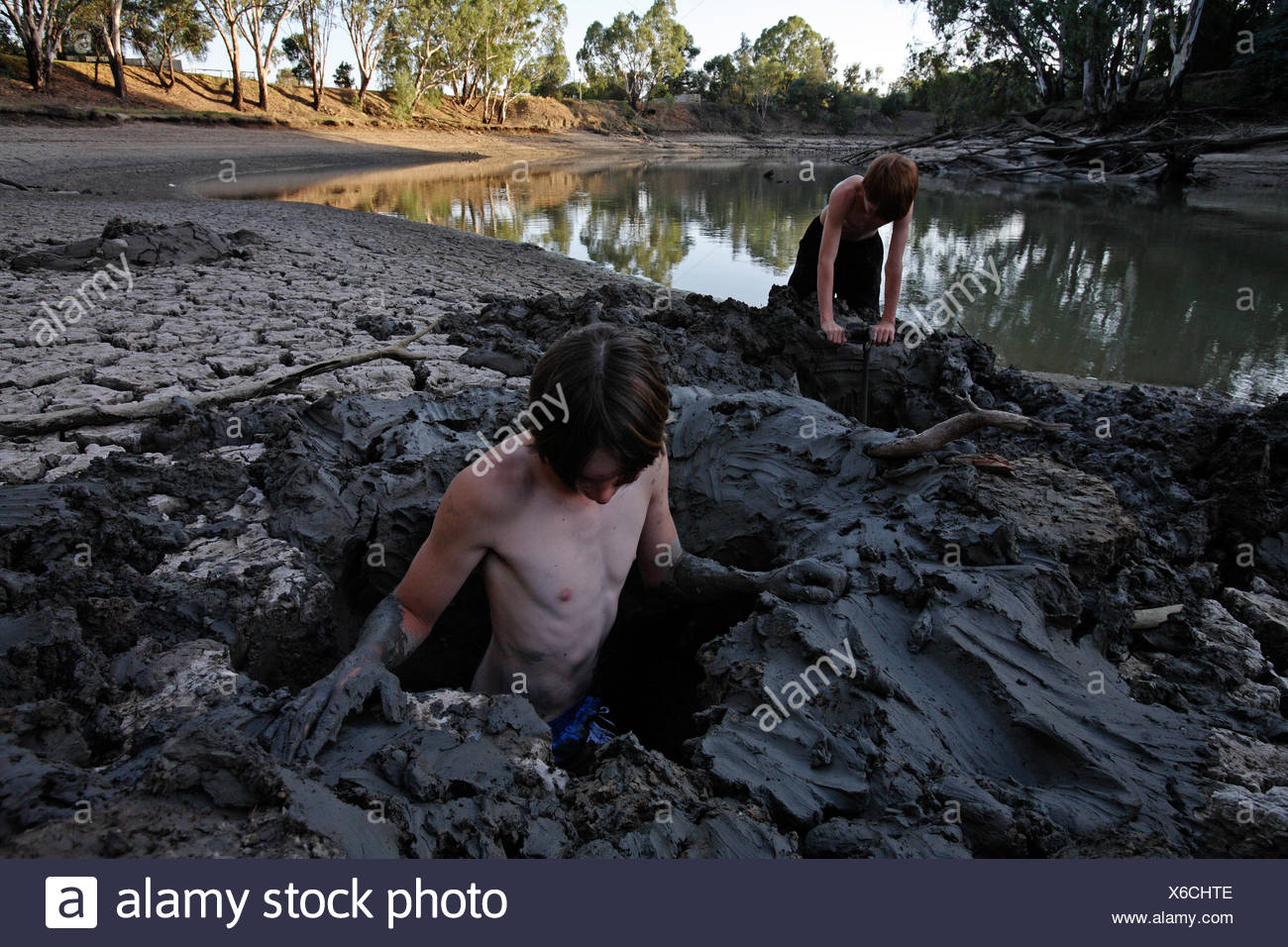 Boys dig holes in the banks of the Murrumbidgee River. - Stock Image