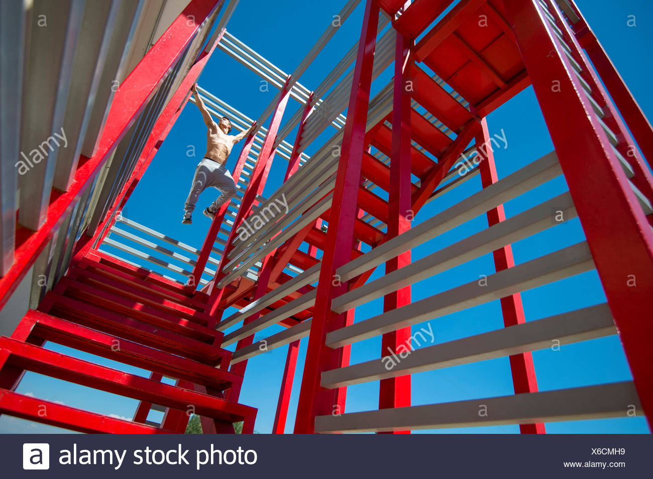 Chase Armitage free running on a red metal structure. - Stock Image
