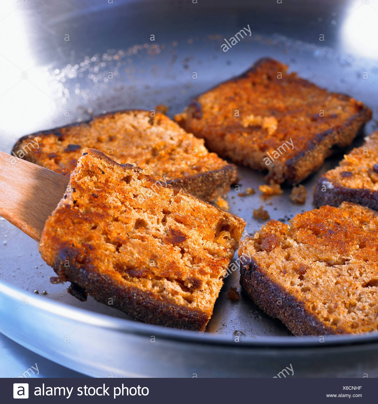 Pan-frying the slices of gingerbread - Stock Image