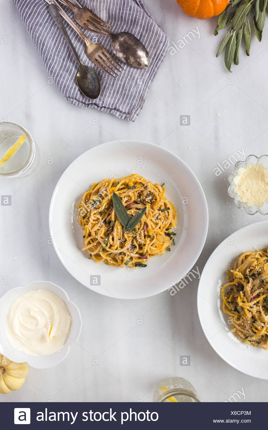 Two bowls of Pumpkin Creme Fraiche Pasta with Sage accompanied with a bowl of creme fraiche are photographed from the top view. - Stock Image