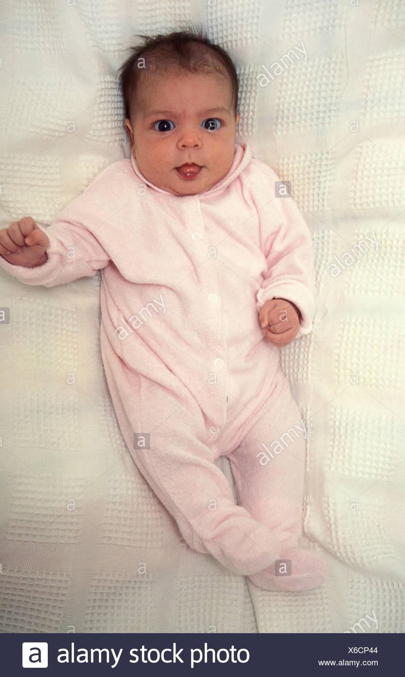 baby girl in pink babygro - Stock Image