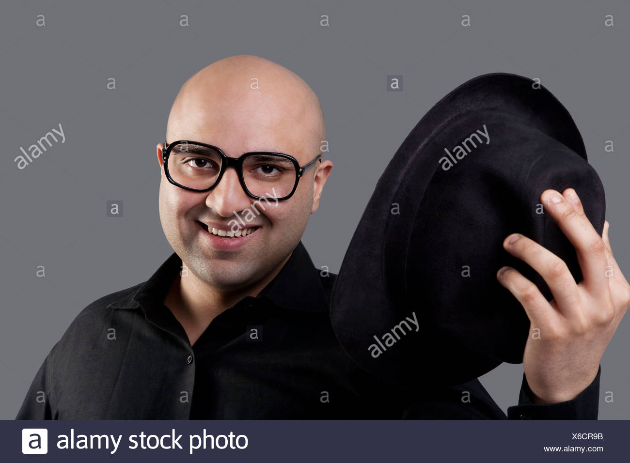 Bald man taking off his hat Stock Photo