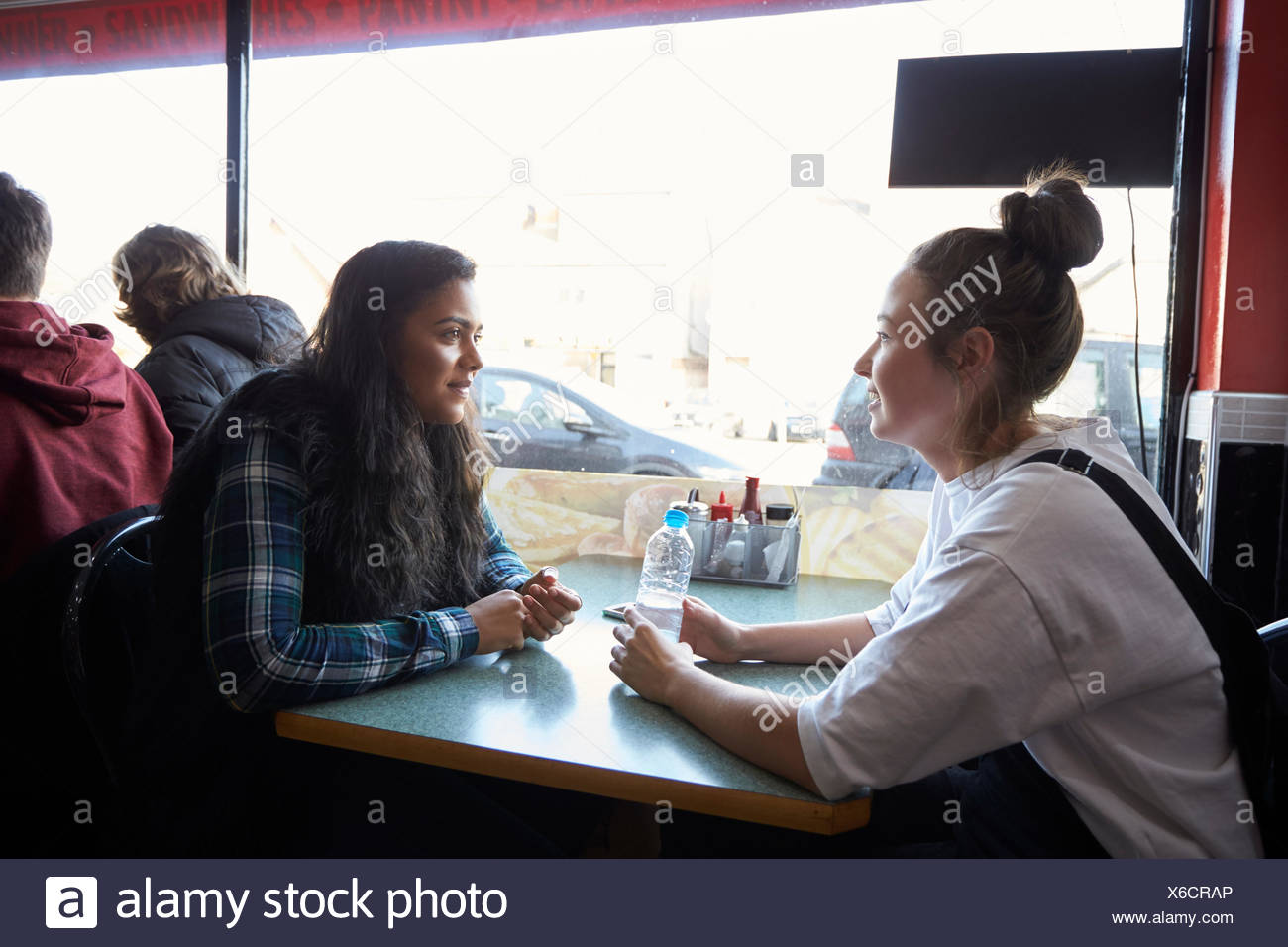 Two Female Students Eating Meal In Café - Stock Image
