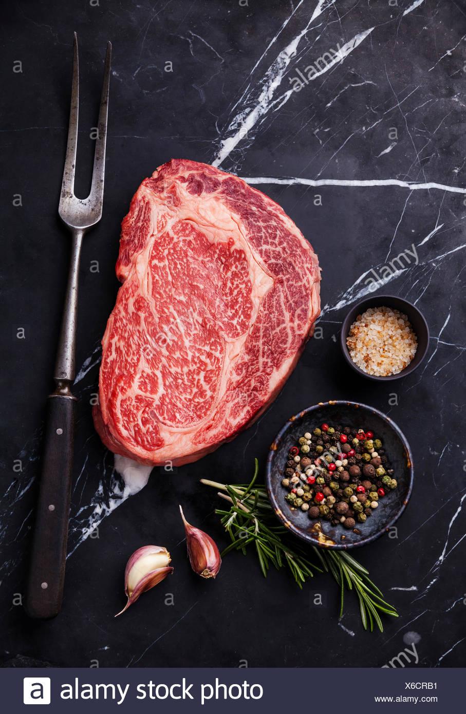 Raw fresh marbled meat Black Angus Steak Ribeye, seasonings and meat fork on dark marble background - Stock Image