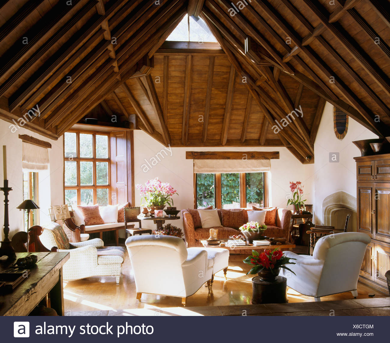 High, vaulted beamed roof in large barn conversion sitting room with white armchairs and sofa and peach Knole sofa - Stock Image