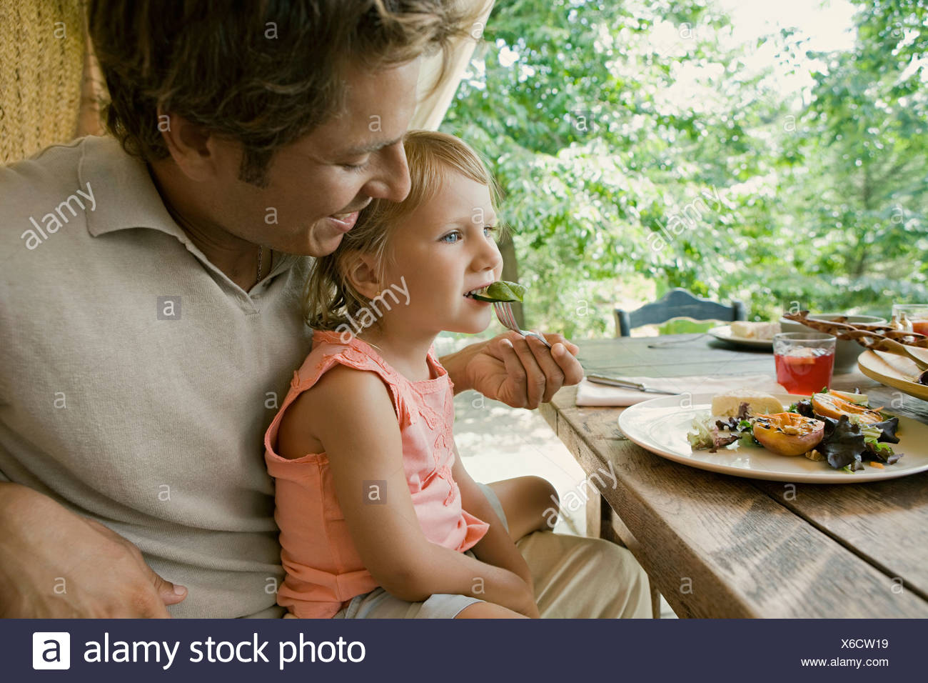 Father feeding daughter at table - Stock Image