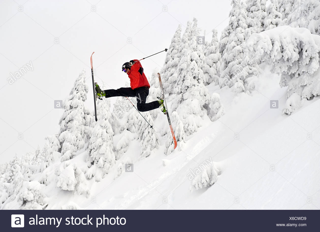 A skier performs a 'daffy'  off a jump at the Eaglecrest Ski area in Juneau, Alaska - Stock Image