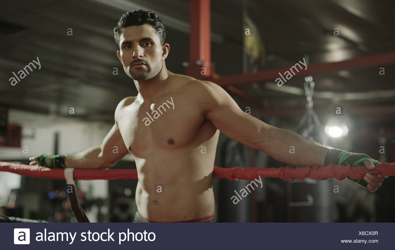 Portrait of serious boxer standing in boxing ring - Stock Image