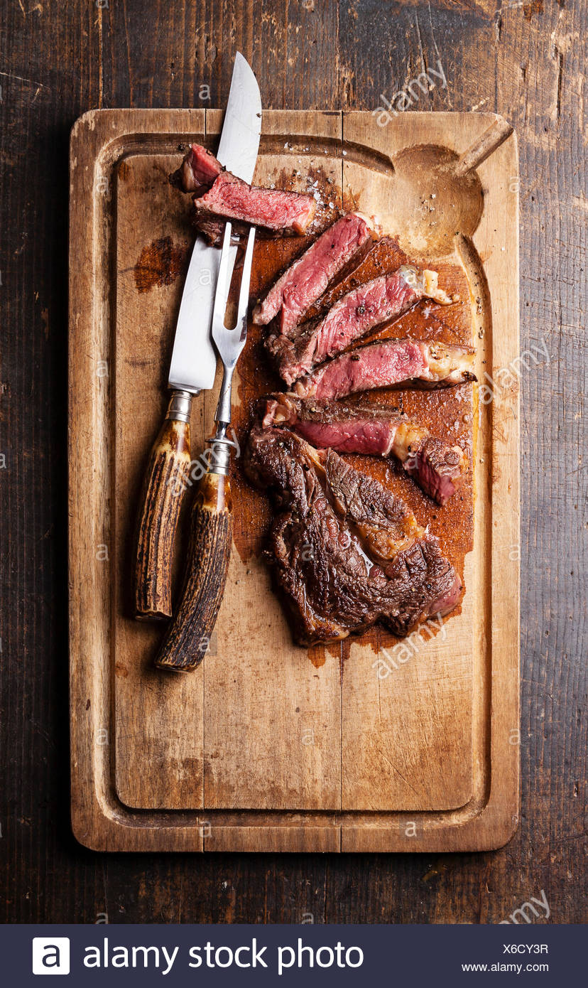 Medium rare Beef steak Ribeye with knife and fork for meat on cutting board on dark wooden background Stock Photo