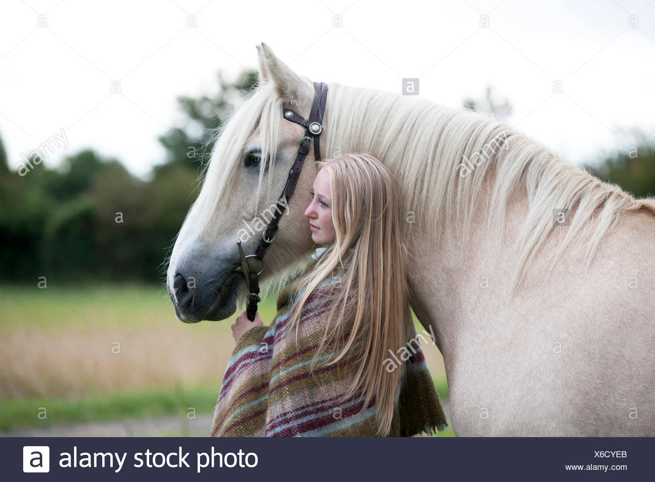 A young woman standing next to a palomino horse - Stock Image