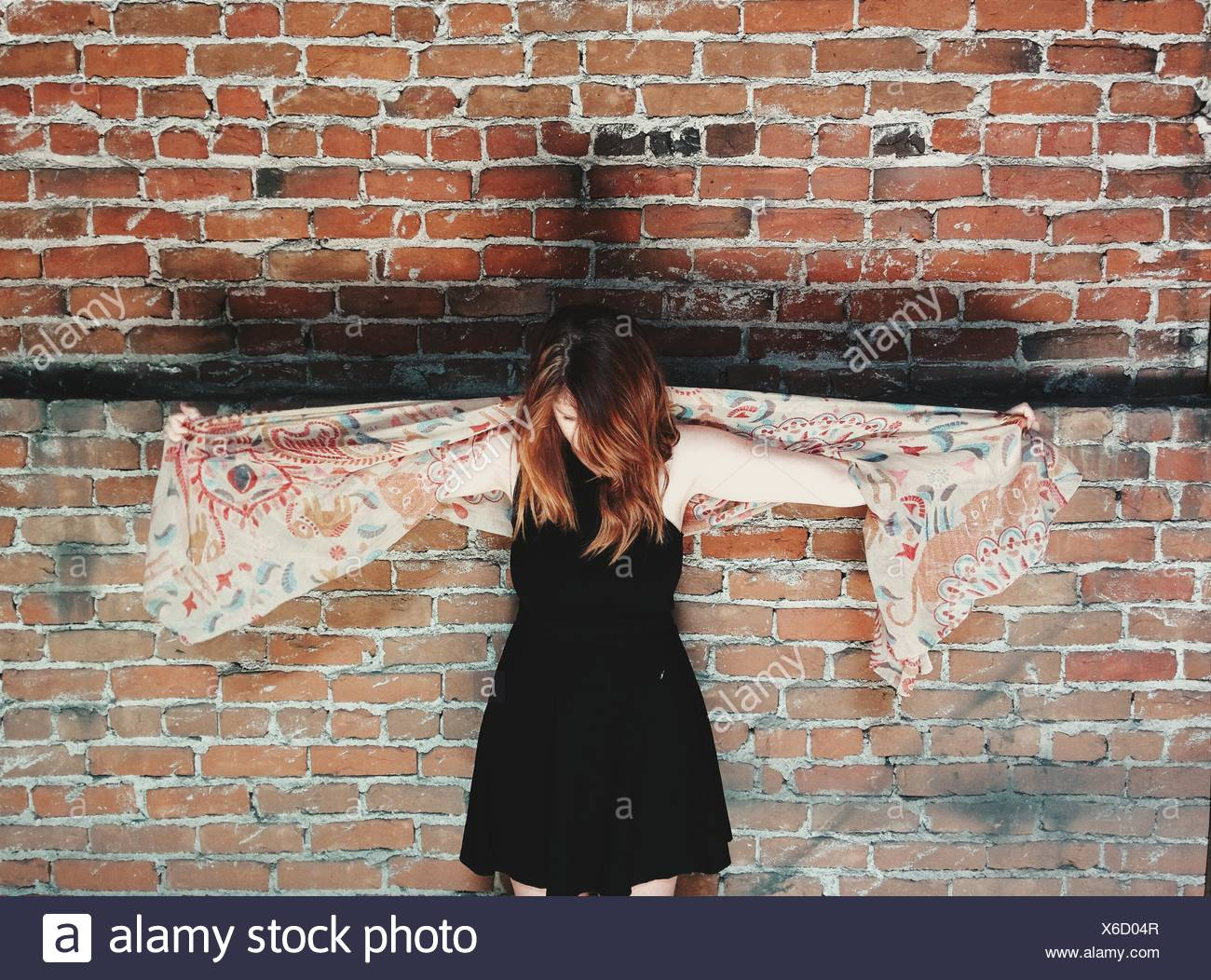 Young Woman Standing Against Brick Wall - Stock Image