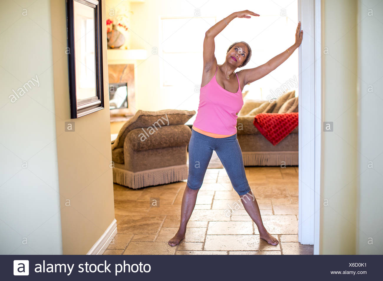 Woman with arms raised doing stretching exercise - Stock Image