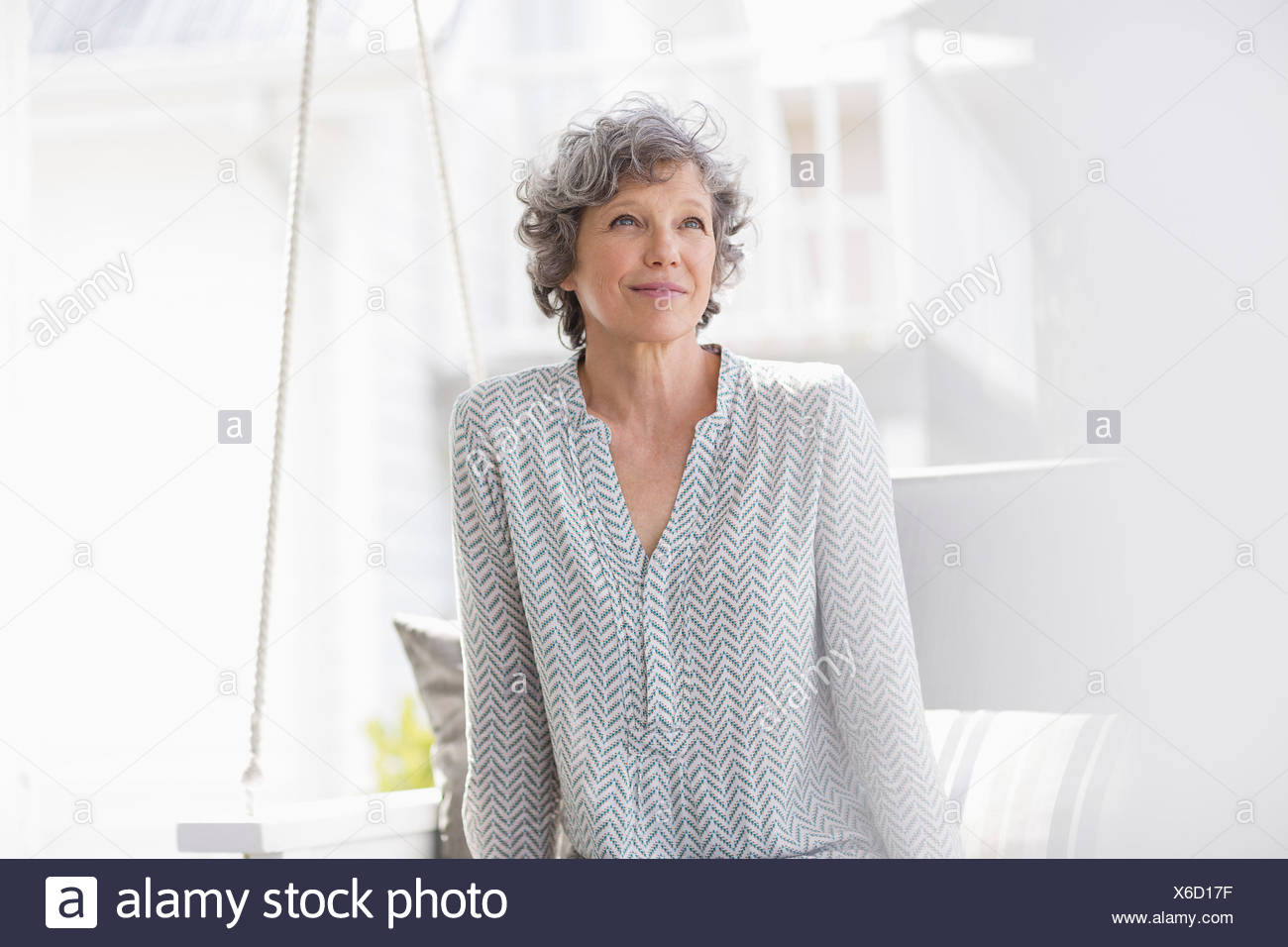 Woman sitting on a swing and thinking - Stock Image