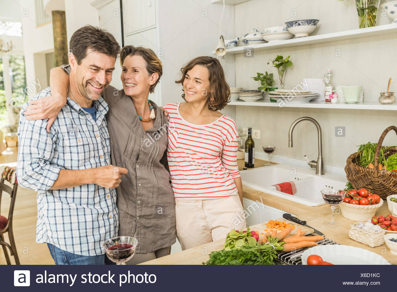 Portrait of three adults preparing fresh vegetables in kitchen - Stock Image