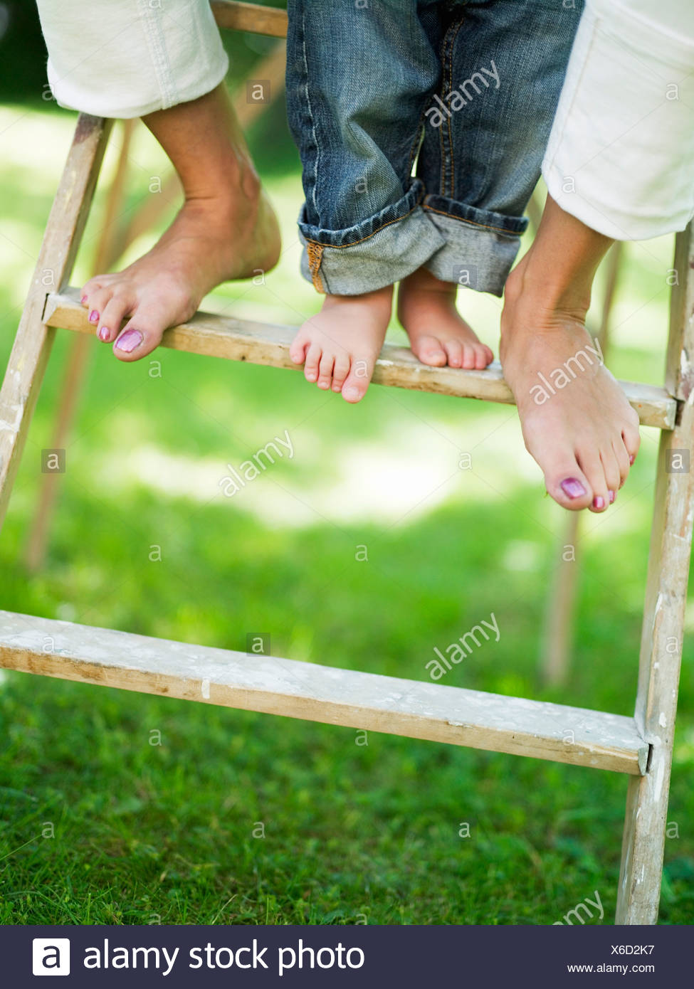 Two pair of legs on a ladder, Stockholm, Sweden. - Stock Image