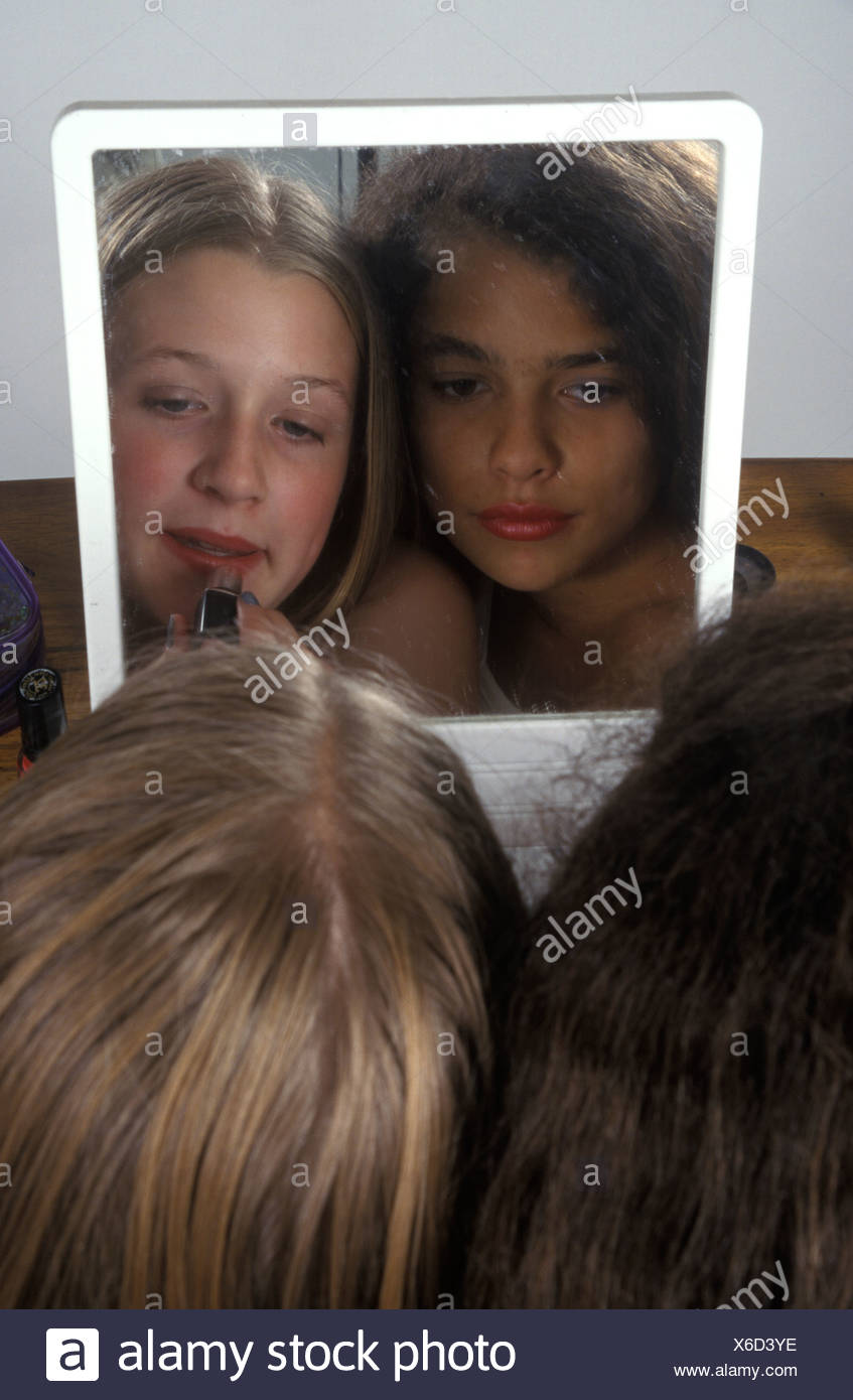 young girls looking at themselves in the mirror - Stock Image