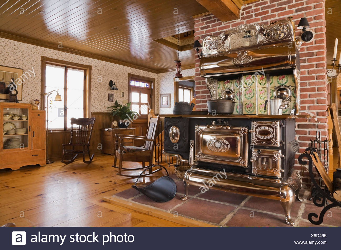 Old Legare's Rural antique wood stove in the living room a Canadiana cottage style fieldstone residential home built to look Stock Photo