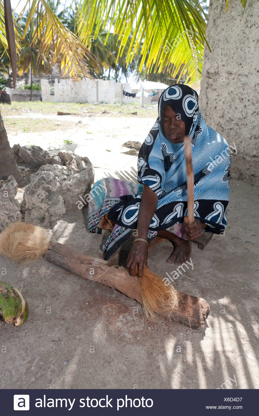 An old woman making a rope out of a coconut shell, Jambiani, Zanzibar, Tanzania, Africa - Stock Image