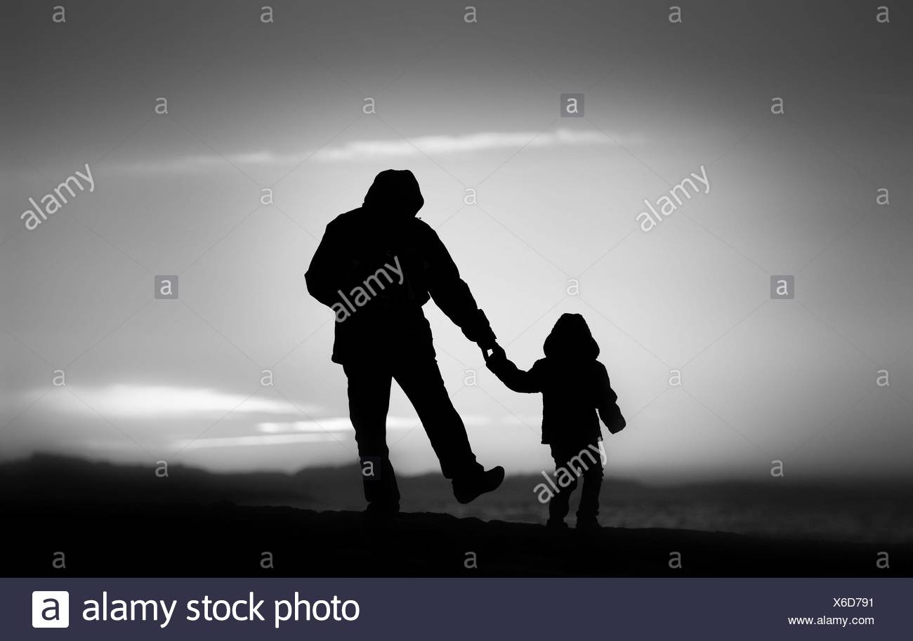 Father and daughter strolling along the beach at sunset. Silhouettes backlit - Stock Image