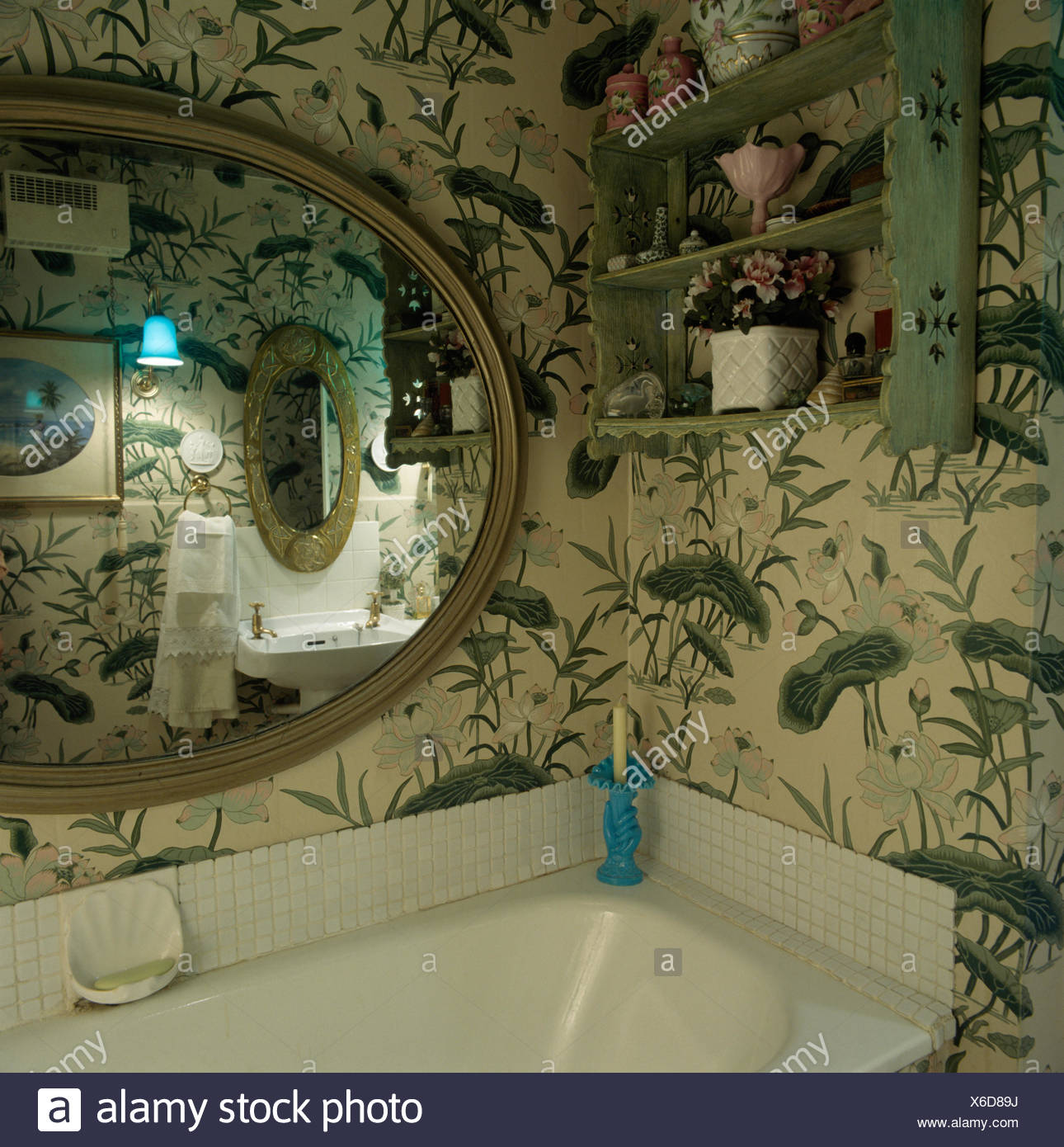 Painted wooden shelves and large oval mirror above the bath in an eighties bathroom with large patterned foliage wallpaper - Stock Image
